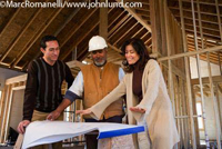 Picture of a man in a white hard hat meeting with a couple and going over the blue prints to their new house being built.